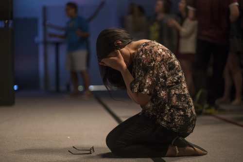 [Woman praying on her knees]